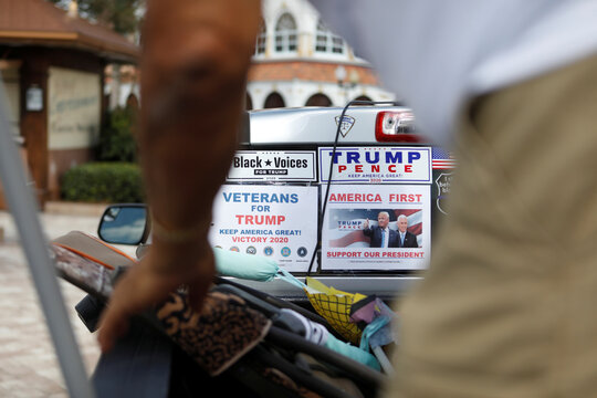 """Guadalupe Aponte Jr., a loyal supporter of U.S. President Donald Trump, prepares to hand out """"Trump for President"""" campaign posters ahead of the election in the retirement community of The Villages, Florida"""