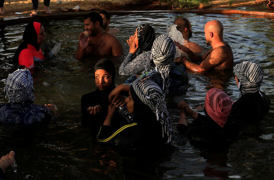 """Egyptians swim in a natural hot water spring which is full of minerals also known as """"Bir Wahed"""" at a Siwa protected area in Egypt's Western Desert, in Siwa"""