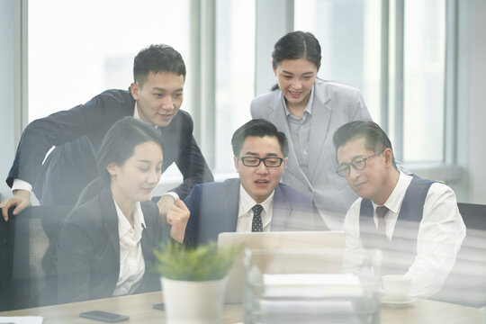 group of asian business people having a discussion using laptop computer