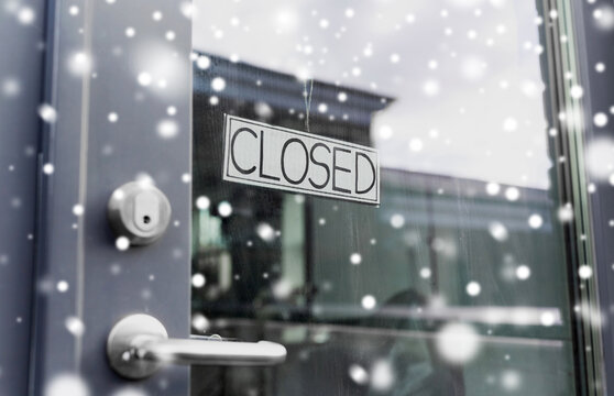 small business, pandemic and service concept - glass door of closed shop or office in winter over snow