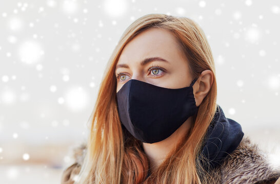 health, safety and pandemic concept - young woman wearing black face protective reusable barrier mask outdoors in winter over snow