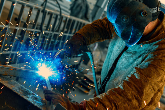 A welder is welding metal parts. Welding and assembly of metal beams
