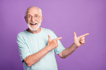 Photo portrait of smiling old man pointing two fingers to side isolated on vivid violet colored...