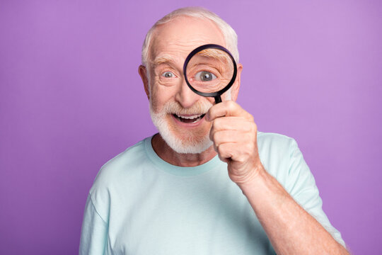 Close-up portrait of cheerful grey beard hair pensioner investigator watching through loup isolated over purple background