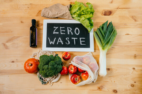Zero waste lifestyle, flat lay, top view on wooden table background with broccoli, salad, leek, apples, pumpkin, glass bottle with soy, black board with text Zero Waste, eco friendly green vegetables.