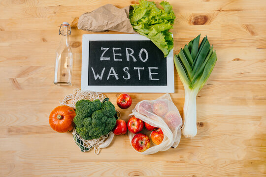 Zero waste lifestyle, flat lay, top view on wooden table background with broccoli, salad, leek, apples, pumpkin, empty glass bottle , black board with Zero Waste text, eco friendly green vegetables.