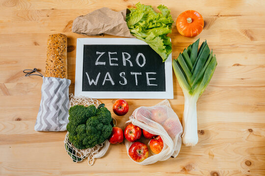 Zero waste lifestyle, flat lay, top view on wooden table background with broccoli, salad, leek, apples, pumpkin, glass bottle olive oil, black board with Zero Waste text, eco friendly green vegetables