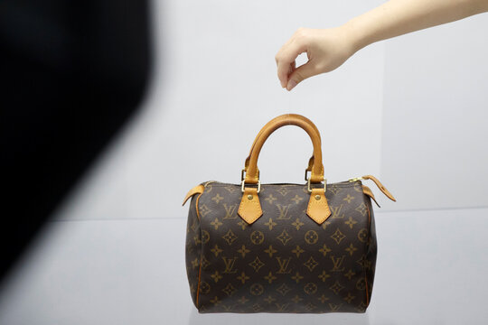 Staff member arranges a handbag during a photoshoot for the second-hand luxury goods retail platform Plum in Beijing