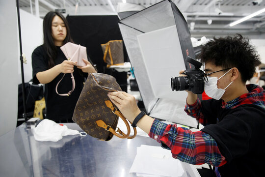 Staff member photographs handbags for the second-hand luxury goods retail platform Plum in Beijing