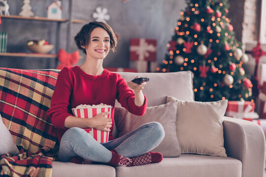 Photo of lovely young lady hold remote control embrace popcorn paper box sitting couch wear red sweater jeans socks indoors