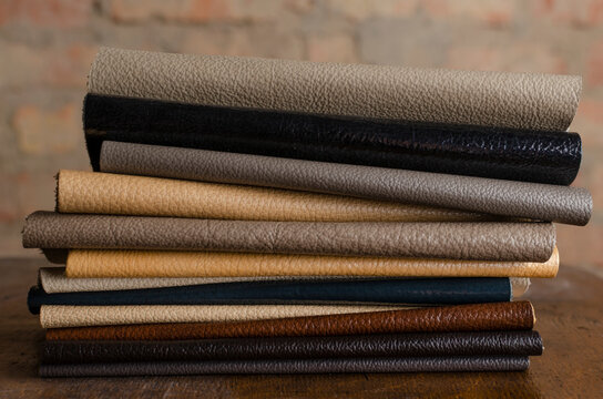 Closeup of stack of brown, beige, grey and dark colored pieces of leather