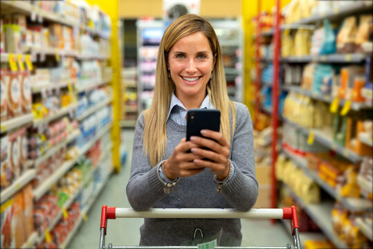 Authentic shot of happy young woman is using a smartphone for online store application and smiling in camera while shopping for groceries in supermarket.