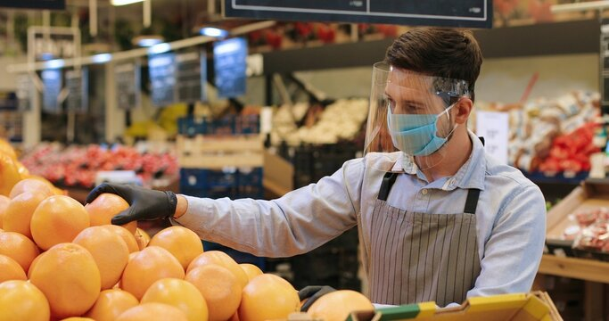 Portrait of male food store employee in face protection shield and apron standing in store and sorting fruits. Handsome Caucasian man seller in mask working indoor. Supermarket concept