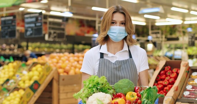 Camera approaching female seller in mask and apron standing in supermarket with packet with food. Close up of beautiful Caucasian woman worker with vegetables in grocery store alone. Retail concept
