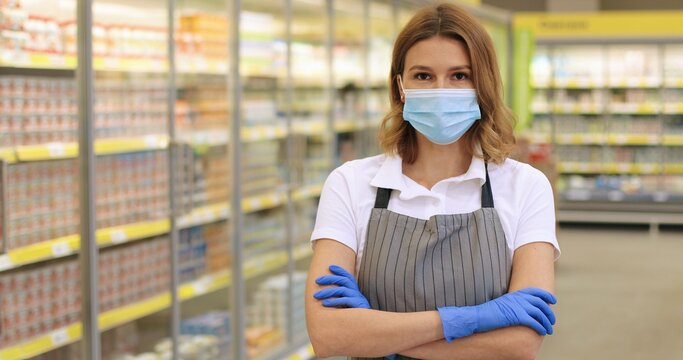 Camera approaching pretty woman supermarket assistant posing indoors. Close up portrait of Caucasian beautiful female employee in mask looking at camera while standing in grocery store. Job concept