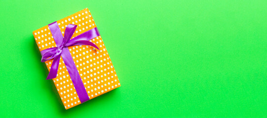 Wall Mural - Top view Christmas present box with purple bow on green background with copy space