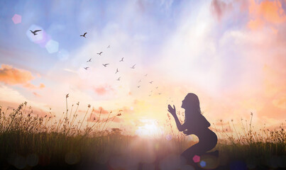 Worship God concept: Silhouette woman kneeling and hand rising on sunset background