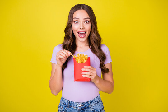 Portrait of attractive amazed hungry cheerful wavy-haired girl eating french fries isolated over bright yellow color background