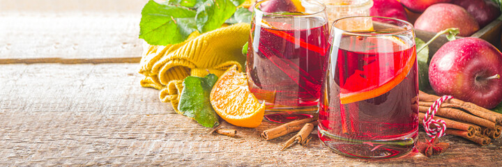 Traditional autumn winter alcohol drink. Hot autumn fruity sangria with citrus, apples and spices, wooden rustic background