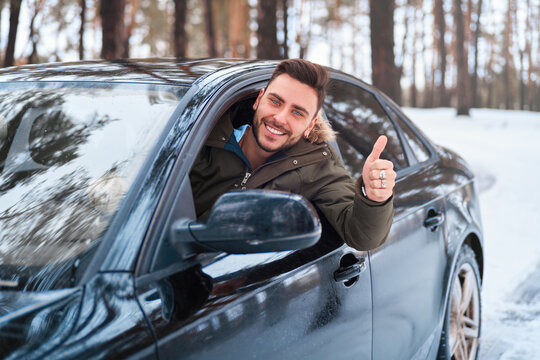 Young attractive Caucasian man sits at the wheel of his car sunny winter day.