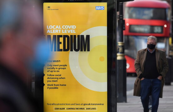 A government local COVID-19 alert level sign is seen at a bus stop in London