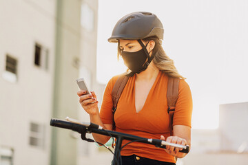 Young adult standing on bicycle using smartphone in the city wearing face mask against COVID-19