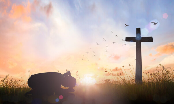 Good Friday concept: Silhouette of prayer woman bow down and praying over cross on sunset background