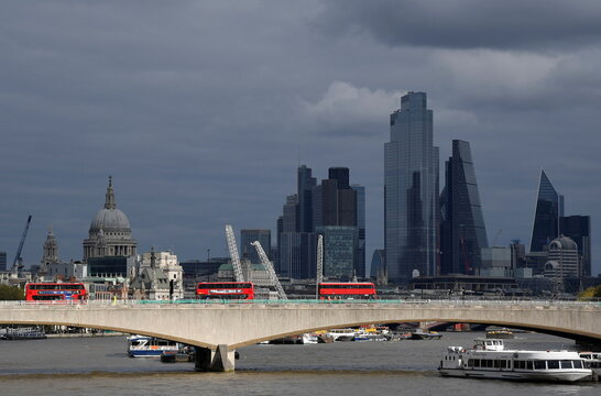 London buses cross Waterloo Bridge as St Paul's Cathedral is seen together with skyscrapers in the City of London financial district