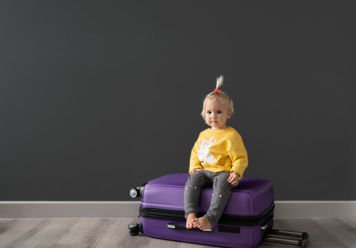 Caucasian cute blond child is sitting at baggage after packing clothes for travel, grey background, copyspace.