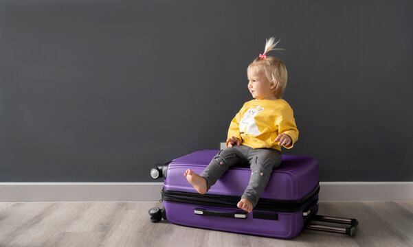 Cute small kid sitting on purple luggage waiting for a trip after lockdown, gray background, copy space.