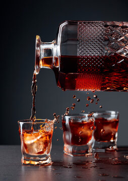 Whiskey pours into a frosted glass with natural ice.