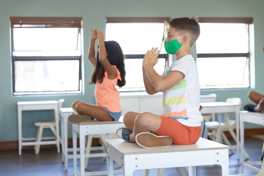 Boy and girl wearing face mask practicing yoga while sitting on the desk in class