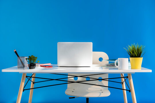Office desk with laptop and blue wall in the background