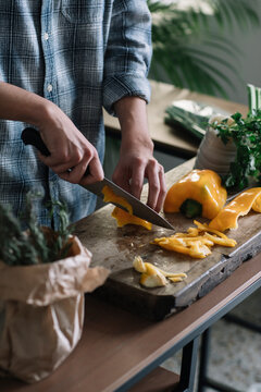 Midsection of young man cutting yellow bell pepper on board in kitchen