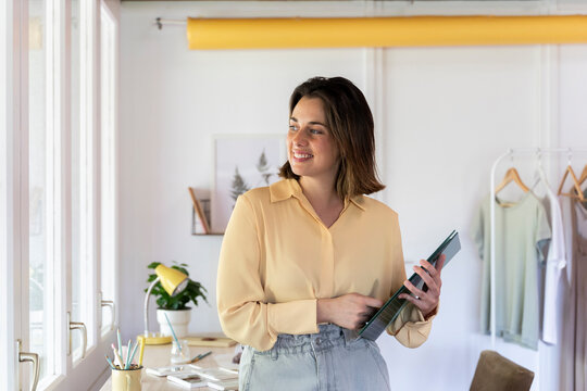 Beautiful smiling young female entrepreneur holding file at clothing store