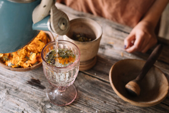 Teapot pouring hot water in herbal tea glass on table