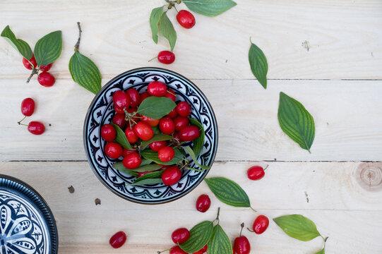 Bowl with leaves and fresh Cornelian cherries (Cornus mas)