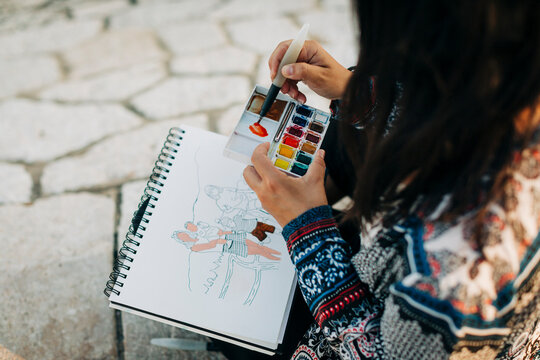 Woman painting with watercolor while sitting at footpath