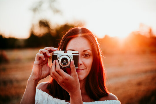 Woman using vintage camera at sunset