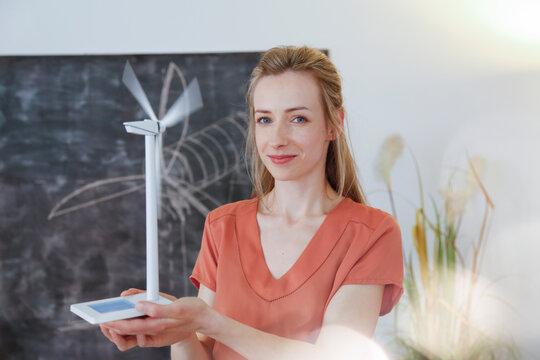 Portrait of confident woman in office holding wind turbine model