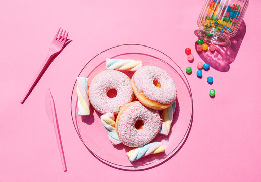 Studio shot of candies spilling out of jar and plate with doughnuts and marshmallows