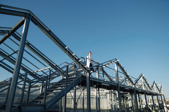 Scientist on a metal construction under blue sky