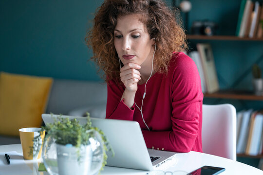 Businesswoman on video conference call looking at laptop while working from home