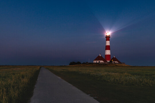 Germany, Schleswig-Holstein, Westerhever, Empty country road stretching past Westerheversand Lighthouse at dusk