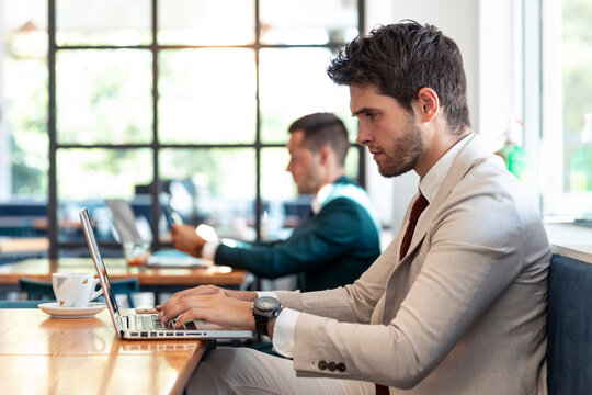 Serious businessman using laptop at table in cafe