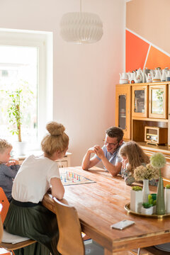 Family playing board game on dining table at home during weekend