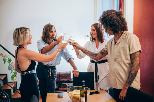 Male and female friends toasting wineglasses during party at home