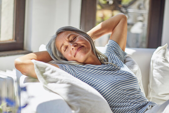 Smiling woman relaxing with eyes closed on sofa in living room