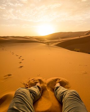 Low angle view of man relaxing on desert landscape during sunset