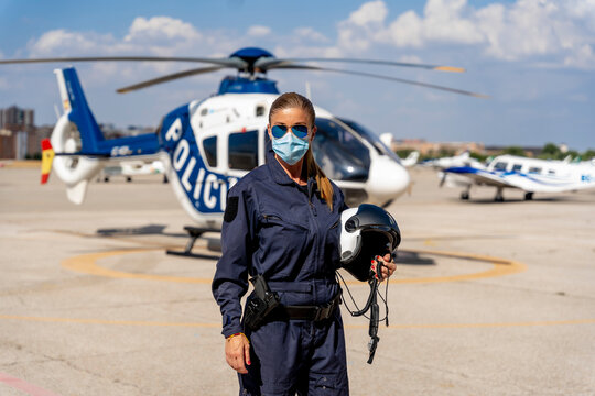 Female police pilot wearing protective face mask while standing against helicopter